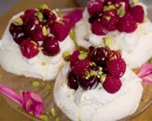 Vegan meringues with coconut cream, berries and pistachio nuts and maple syrup